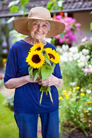 Portrait of a Happy Senior Woman in Blue Clothing with Garden Hat Holding Pretty Sunflowers