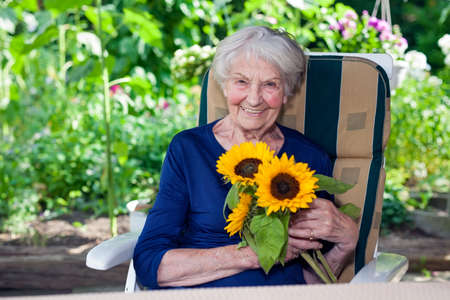 Close up Happy Old Lady in Blue Dress, Sitting on a Chair at the Garden, Holding Fresh Sunflowers While Looking at the Camera.