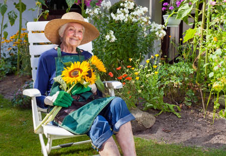 Smiling Old Woman with Hat, Apron and Gloves for Gardening Sitting on a White Chair Holding a Bouquet of Sunflowers, Looking at the Camera.