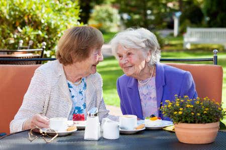 persona de la tercera edad: Dos feliz Mujeres mayores sentarse y charlar en la mesa al aire libre con café y aperitivos