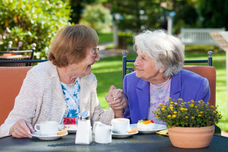 amigos hablando: Dos mujeres de edad avanzada feliz que charla en la Mesa de jardín con café y aperitivos mientras sujeta las manos.