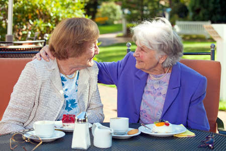 Two Cheerful Senior Best Friends Talking at the Outdoor Table Closely with Coffee and Snacks While One is Holding the Shoulder of the Other.