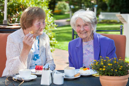 frail: Close up Two Stylish Cheerful Elderly Women Relaxing at the Outdoor Table with Coffee and Snacks