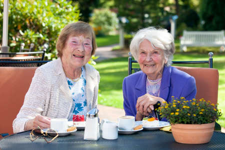 socialising: Close up Two Happy Senior Ladies Sitting at the Garden Table with Snacks While Looking at the Camera. Stock Photo