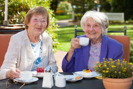 가 까이 서 두 행복 한 수석 여자 정원 테이블에서 커피 시간을 보내고 카메라를 찾고. 스톡 콘텐츠
