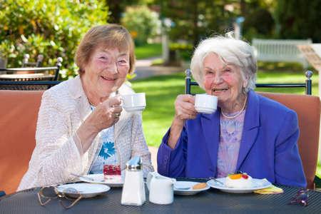 Twee oudere vrouwelijke Beste Vrienden Zittend aan de Outdoor tafel terwijl Holding kopjes koffie en glimlachen naar de camera. Stockfoto