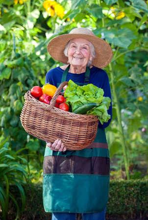 Portret van een senior vrouw in Tuinieren Outfit met Mand van gezonde verse groenten in de tuin terwijl lachend op de camera Stockfoto