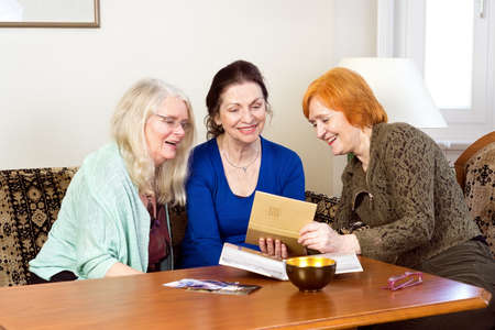 old photograph: Three Happy Middle Age Women Sitting at the Living Area Looking at their Old Photograph in a Photo Album.