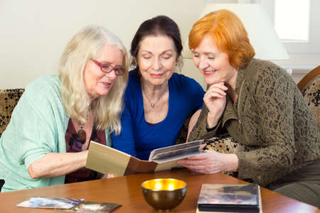 happy moment: Close up Three Middle Age Female Friends Sitting at the Living Area Looking at Photo Album Together and Talking Happy Moment in the Past.