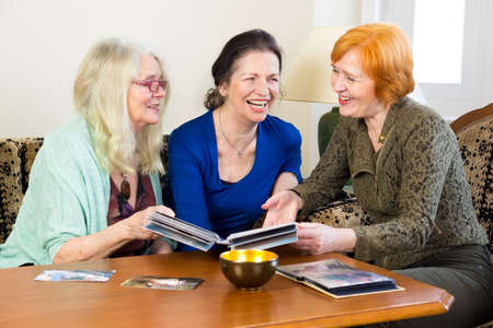 mementos: Three Adult Women Friends, Relaxing at the Living Area, Laughing Together While Looking at their Old Photos in an Album. Stock Photo