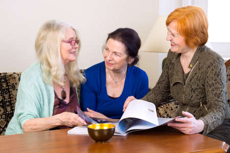 middle age women: Three Middle Age Women Best Friends Enjoying their Talks at the Living Area While Scanning a Magazine.