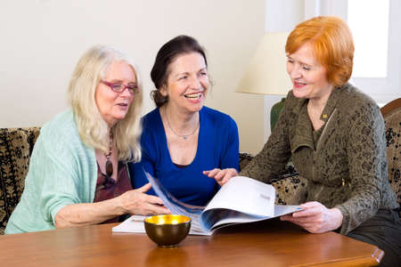 group discussions: Three Happy Adult Female Friends Enjoying at Home While Scanning a Magazine on the Table. Stock Photo