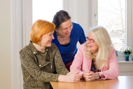 amigos hablando: Cierre de Tres felices Media Edad amigos de las mujeres que disfrutan de su Girl Talk en la madera Mesa de comedor dentro de un restaurante.