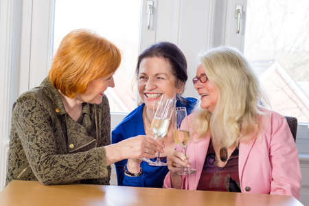 hilarity: Three Happy Middle Age Mom Best Friends Tossing Glasses of White Wine and Smiling Each Other While Sitting at the Wooden Table Inside a Restaurant. Stock Photo