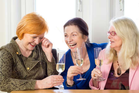 hilarity: Three Happy Adult Female Friends Laughing at their Funny Conversation About their Past at the Table with Glasses of White Wine.