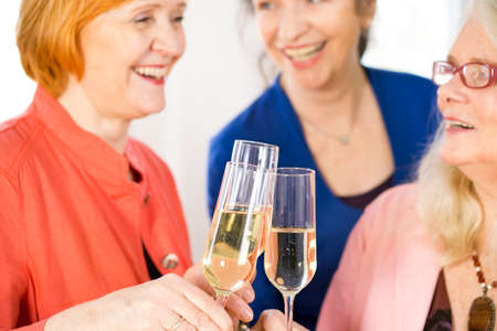 middle age women: Close up Glasses of Tasty White Wine Tossed by Happy Adult Lady Friends to Celebrate Something. Stock Photo