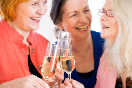 boomer: Close up Three Happy Adult Mom Friends Celebrating Something with Glasses of White Wine