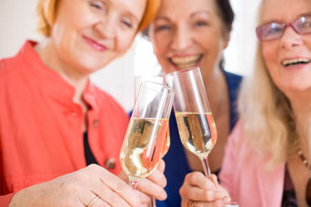 inebriated: Three Smiling Mom Friends Tossing Glasses of Champagne, Celebrating their Friendship. Captured in Macro.