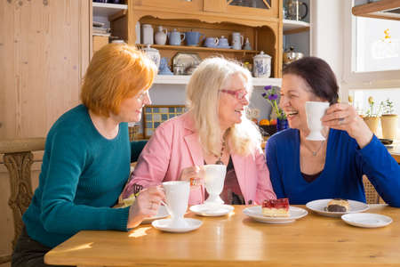 chat group: Three Cool Middle Age Female Friends Having Snacks at the Cafe While Talking Something Interesting.
