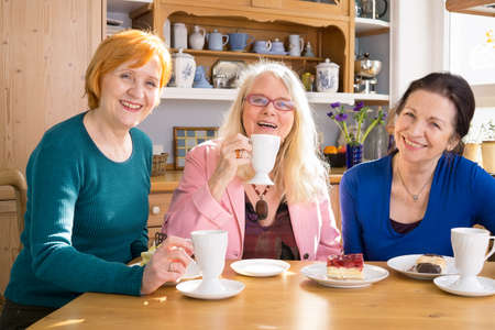 Three Smiling Mom Friends Sitting at the Wooden Table with Tasty Snacks and Looking at Camera