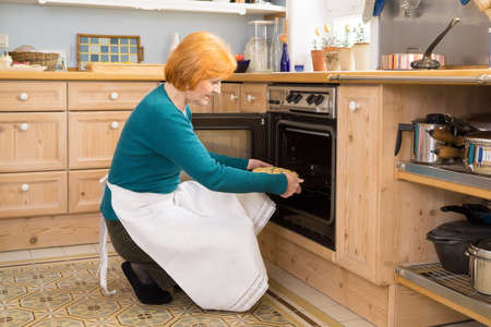 placing: Blond Middle Age Woman With Apron Putting a Cake for Snacks in an Oven at the Home Kitchen. Stock Photo