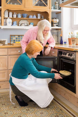 Serious Mom Watching her Happy Active Friend Putting a Cake for their Snacks in an Oven at the Kitchen.