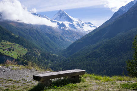 valais: Bench with Scenic View of Snow Capped Alps and Overview of Lush Green Mountain Valley on Bright Sunny Day Valais Switzerland.