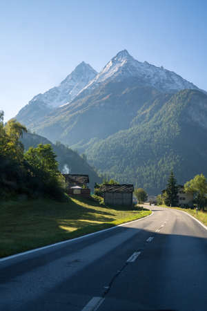 highroad: Quaint Houses Along Paved Mountain Road Through Lush Green Valley with Snow Capped Alps Valais Switzerland on Sunny Day.