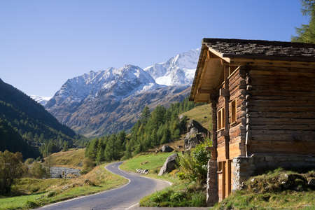 single lane road: Quaint Wood Cabin Beside Paved Single Lane Mountain Road Through Snow Capped Alps Valais Switzerland. Stock Photo