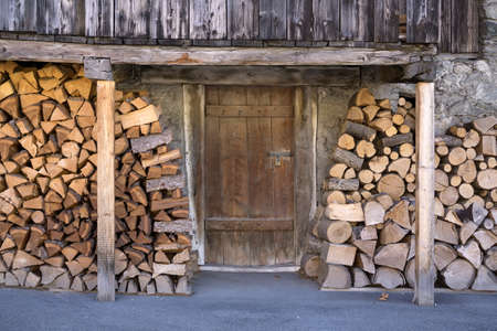 provisions: Fire Wood Stacked Outside Rustic Rural Barn with Closed Wooden Door