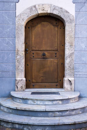 architectural exterior: Architectural Exterior Detail of Closed Arched Wooden Door of Building Constructed from Blue Stone Marble with Steps Stock Photo