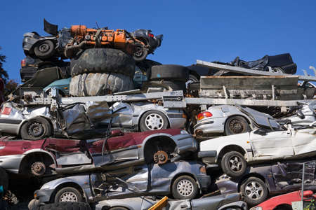 junk yard: Low Angle View of Old Squashed Cars Stacked at Junk Yard with Blue Sky in Background