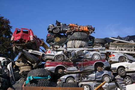 motorcars: Scrap yard for obsolete Motorcars with old wrecks and stripped vehicles piled high into the air on top of one another under a sunny blue sky.