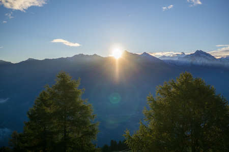sun flare: Scenic Spectacular landscape with sunshine and lens flare above the Alps Mountains and evergreen coniferous trees under a serene blue sky. Stock Photo