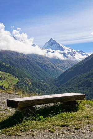 dent: Rustic wooden bench overlooking the snow capped summit of Dent Blanche in the Pennine Alps in the canton of Valais Switzerland. Stock Photo