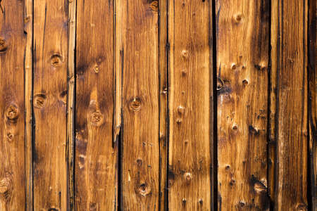 treated board: Vertical brown wooden panels on the exterior wall of a rustic house from countryside closeup.