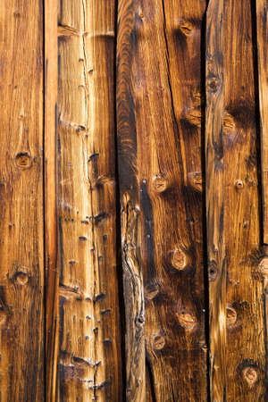 treated board: Brown spotted wooden wall made of lacquered hardwood boards disposed vertically architectural closeup from Thyon Valais Switzerland Stock Photo