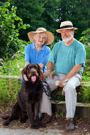 Smiling White Senior Couple Sitting at the Garden with their Black Dog Pet and Looking at the Camera.