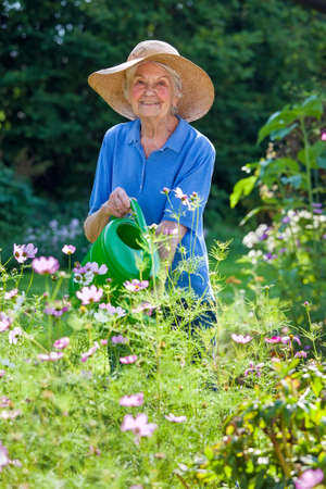 Smiling Senior Woman, Wearing Brown Hat, Watering her Flower Plants at the Garden While Looking at the Camera.