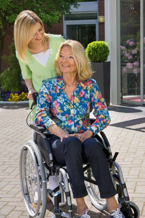 handicapped accessible: Blond Nurse Standing Behind Senior Woman in Wheelchair with Hand on Shoulder Outdoors in front of Building on Sunny Day Stock Photo