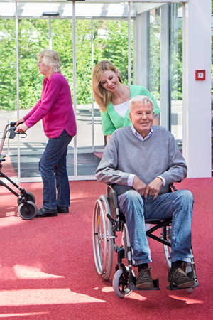 mobility nursing: Portrait of Smiling Blond Nurse Pushing Senior Man in Wheelchair Through Lobby of Retirement Building with Woman in Background Passing By with Walker Stock Photo