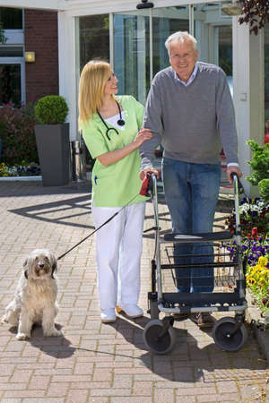 mobility nursing: Smiling Blond Nurse Holding onto Arm of Senior Man, Helping Man with Walker Walk Dog on Leash Outdoors in front of Retirement Building on Sunny Day