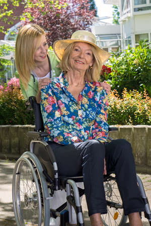 eldercare: Blond Nurse Standing Behind Senior Woman in Wheelchair Wearing Sun Hat in front of Retirement Building, Enjoying the Day Stock Photo