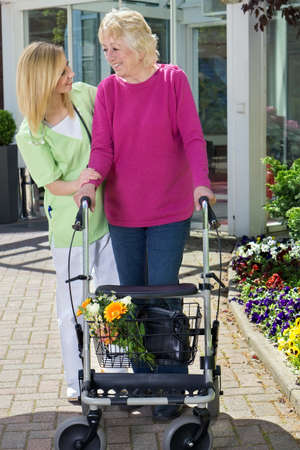 holding in arm: Blond Smiling Nurse Holding Arm of Senior Woman with Walker, Helping Senior Resident to Walk Outdoors in front of Building Entrance Near Flower Beds and Showing Care and Concern Stock Photo