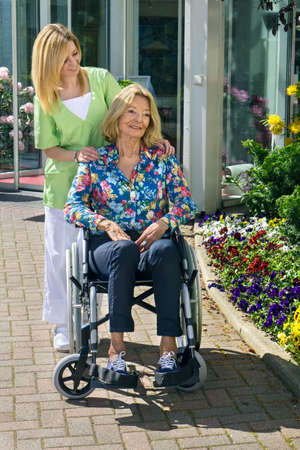 mobility nursing: Blond Nurse Standing Behind Senior Woman in Wheelchair with Hands on Shoulders Outdoors in front of Building on Sunny Day Stock Photo