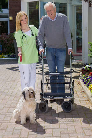 Smiling Blond Nurse Holding onto Arm of Senior Man, Helping Man with Walker Walk Dog on Leash Outdoors in front of Retirement Building on Sunny Day