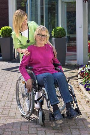 Prendre soin Blonde infirmière debout derrière senior femme en fauteuil roulant avec la main sur l'épaule extérieur en face du bâtiment sur Sunny Day Banque d'images - 42262163