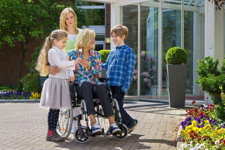 Happy cute caring grandchildren with concerned mother visiting youthful looking grandmother in wheelchair