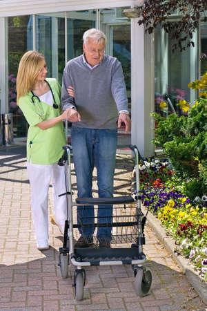 jardines flores: Enfermera sonriente rubio ayuda al hombre mayor a caminar con Walker, estabilizando Hombre con Walker Aire libre delante del edificio con jardines de flores