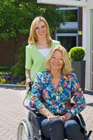 mobility nursing: Portrait of Blond Nurse Pushing Senior Woman in Wheelchair in front of Building Entrance on Sunny Day